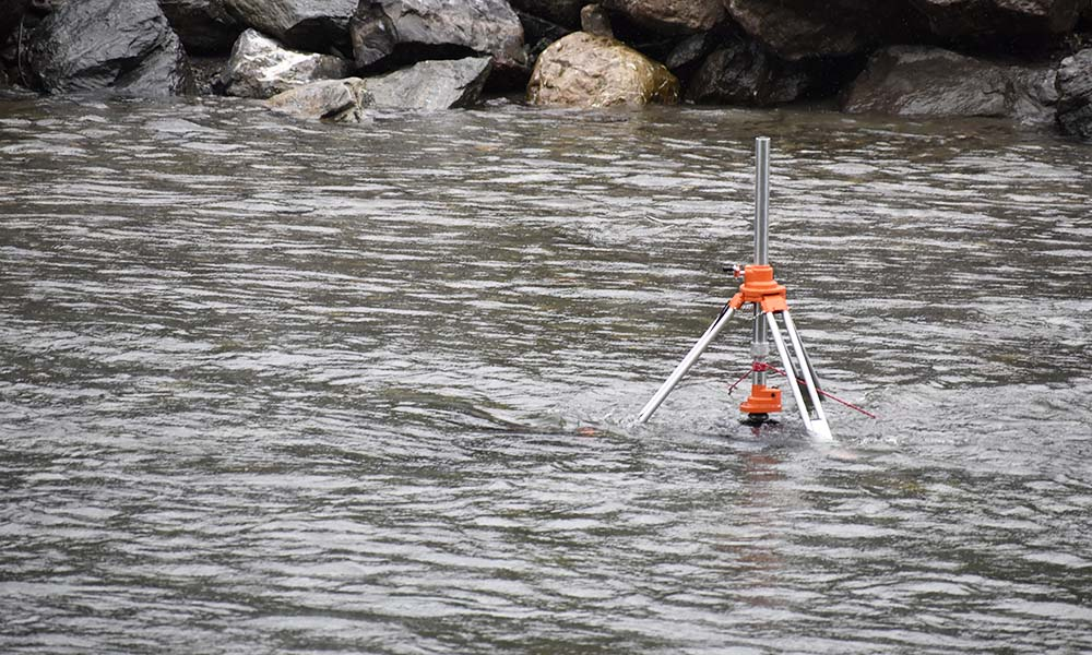 A silver tripod with orange parts sits in the Vedder River. It is a sonar system used by the Sumas First Nation.