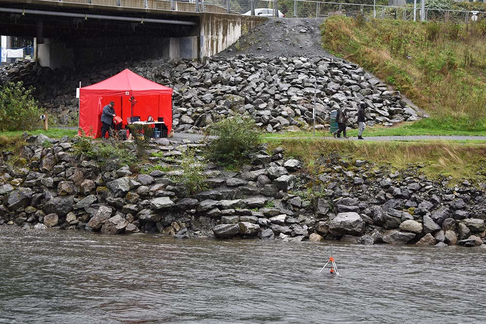 A red tent on the bank of the Vedder River. In the water, a tripod sonar system.