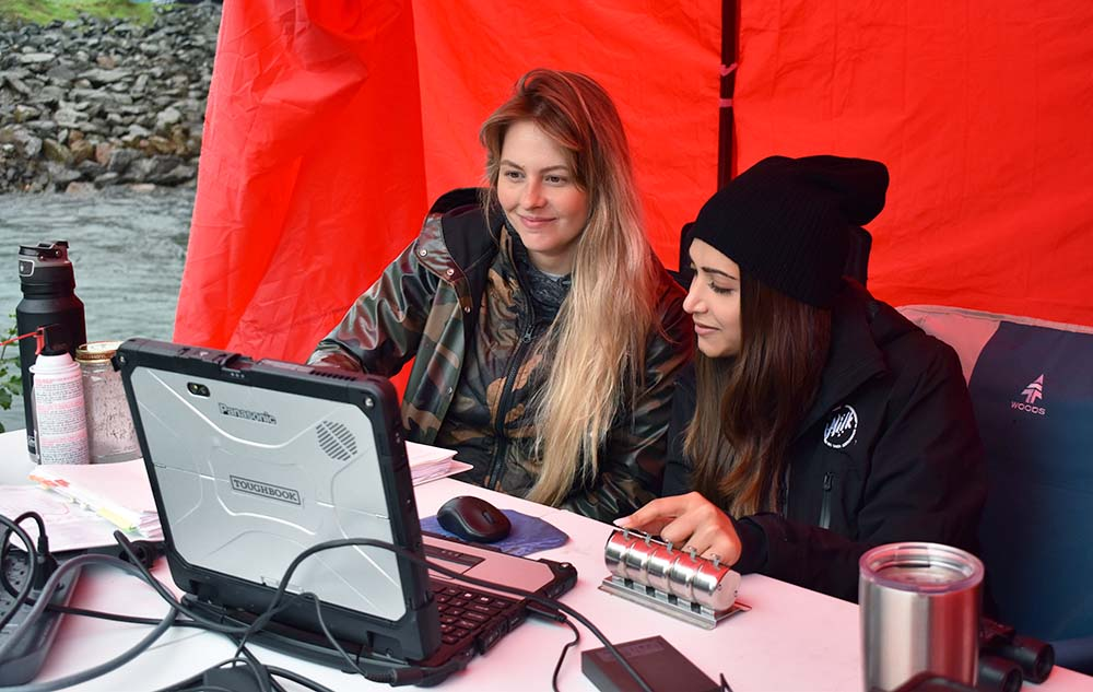 Amanda Gawor (left) and Philipa Dutt (right) look at the computer underneath a red tent.