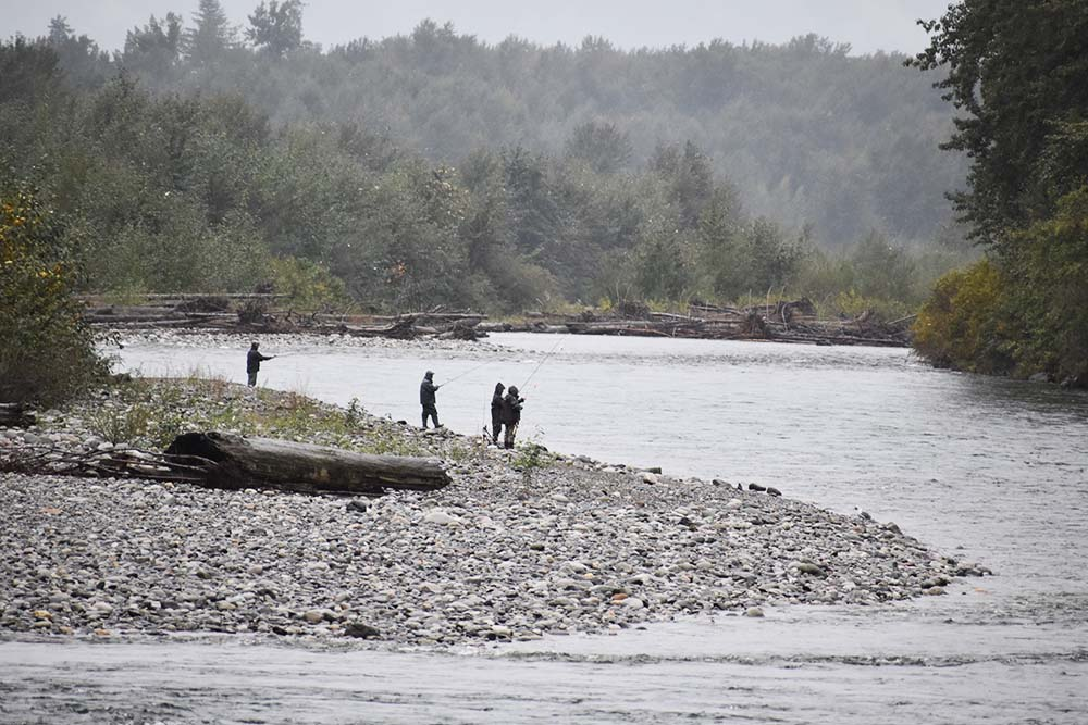 Fishers standing on the gravel bank of the Vedder River in the rain.